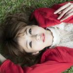 草原に寝そべる若い女性