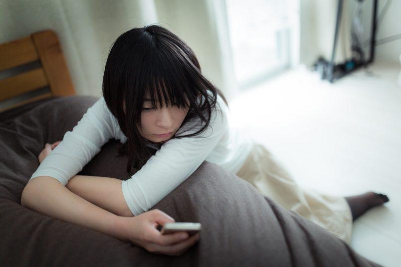 呆然と携帯を見る女性