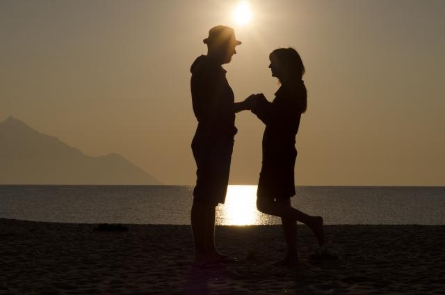 海辺で手を繋ぐ男女