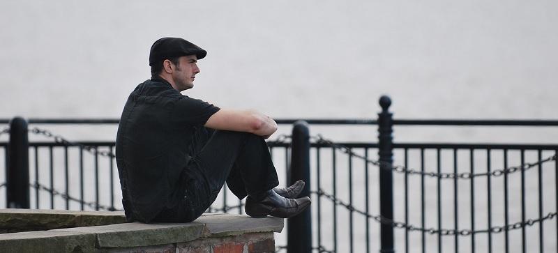 膝を抱えて座る男性