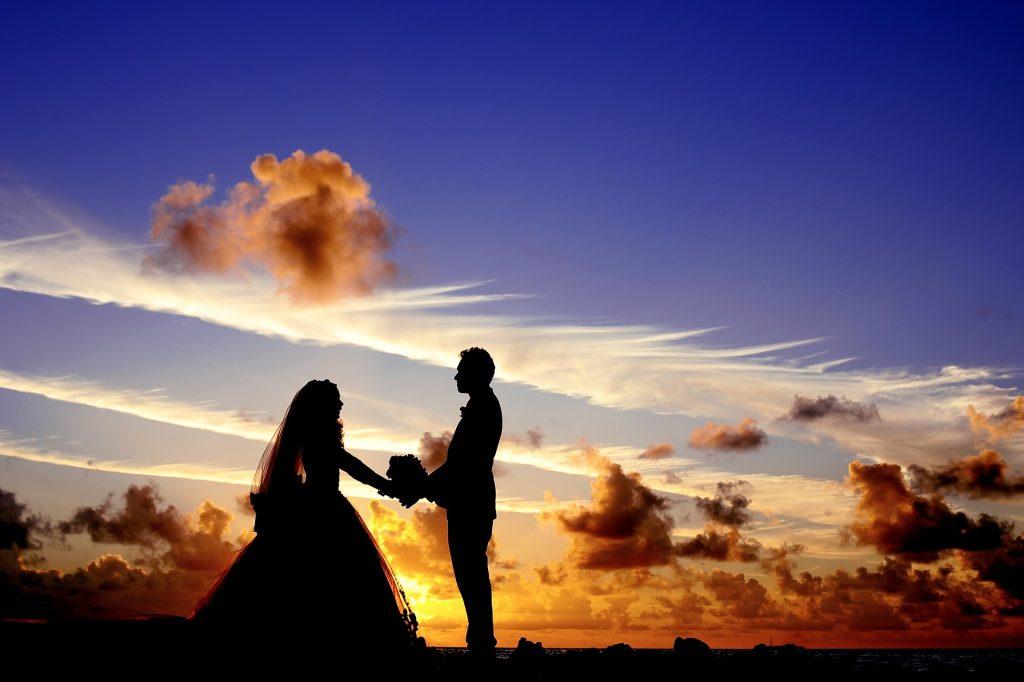 夕暮れの空をバックに男性が女性に花束を渡している